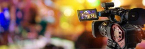 Filmkamera steht vor einem verschwommenen Hintergrund und filmt eine Szene