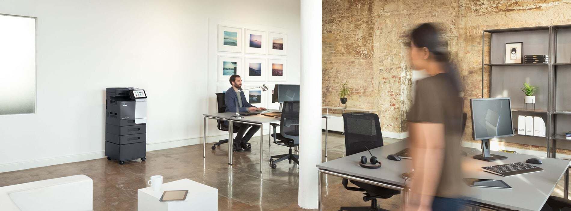 So finden Sie den richtigen Drucker fürs Büro: Frau steht am Bürodrucker in einem großen Büro und holt ihren Ausdruck, Mann sitzt am Schreibtisch und arbeitet