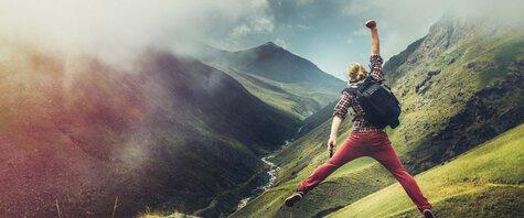 Mann springt mit ausgestreckter Faust vor Bergkulisse