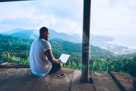 a man is sitting on a terrace with laptop and with a view