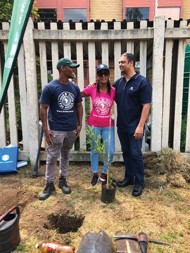 FTFA representatives Jeminah Mkhize and Teboho Mosehle with Craig Williams, national technical & training manager at Konica Minolta SA, showing the pupils of AB Xuma School how to plant and care for a tree.