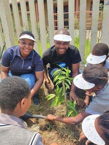 Tebogo Mbiza, national workshop technician at Konica Minolta SA and William Mabokela national warehouse supervisor at Konica Minolta SA, planting trees with the pupils of AB Xuma School.