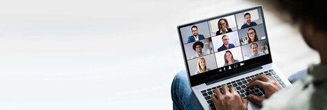 Mann mit einem Laptop nimmt an einer Video-Konferenz teil und schaut den anderen Teilnehmern beim Meeting zu